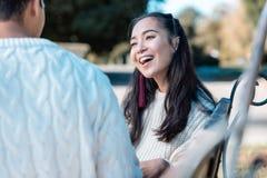 Persona femminile dai capelli lunghi allegra che ascolta il suo partner fotografia stock libera da diritti