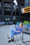 Persona femminile felice che si siede nella sedia con il fondo della costruzione Fotografia Stock