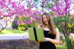 Persona femminile intelligente che utilizza computer portatile nel fondo di fioritura Fotografia Stock