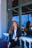 Persona femminile piacevole che sta finestra vicina del caffè della via Immagine Stock