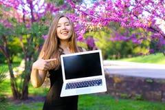 Persona femminile sorridente che mostra computer portatile moderno con il fondo di fioritura del parco Immagine Stock