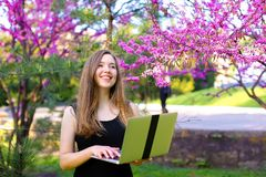 Persona femminile sorridente che utilizza computer portatile nel fondo di fioritura Fotografie Stock Libere da Diritti