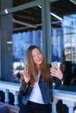 Persona femminile sveglia che fa video chiamata dallo smartphone al caffè Immagini Stock Libere da Diritti