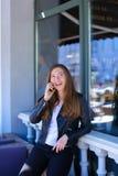Persona femminile sveglia che parla dallo smartphone vicino alla finestra del caffè della via Immagini Stock Libere da Diritti
