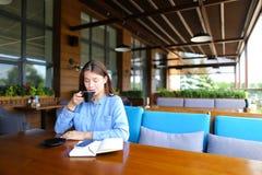 Persona femminile sveglia che si siede al caffè con il caffè dello smartphone e del taccuino e di bevanda Fotografia Stock Libera da Diritti