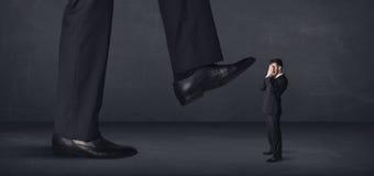 Persona gigante que camina en un concepto del pequeño hombre de negocios Imagenes de archivo