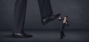 Persona gigante que camina en un concepto del pequeño hombre de negocios Fotos de archivo libres de regalías