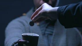 Persona hearted gentile che dona i centesimi alla tazza della tenuta del mendicante, carità al senzatetto video d archivio