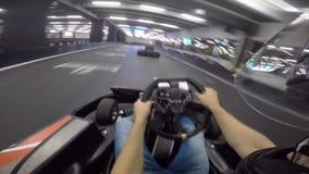 Persona hermosa pov del hombre joven primera que conduce el coche del kart del ocio en la acción extrema karting del deporte de l almacen de video