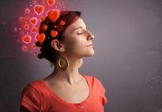 Persona joven que piensa en amor con los corazones rojos Fotografía de archivo