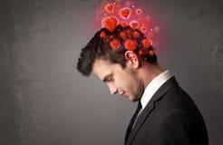 Persona joven que piensa en amor con los corazones rojos Imagen de archivo