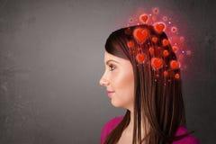 Persona joven que piensa en amor con los corazones rojos Imágenes de archivo libres de regalías