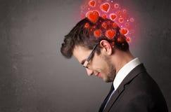 Persona joven que piensa en amor con los corazones rojos Imagenes de archivo