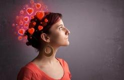 Persona joven que piensa en amor con los corazones rojos Foto de archivo libre de regalías