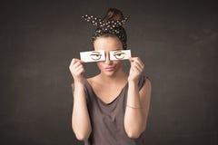 Persona joven que se sostiene de papel con el dibujo enojado del ojo Foto de archivo libre de regalías