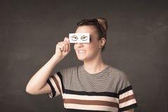 Persona joven que se sostiene de papel con el dibujo enojado del ojo Fotos de archivo libres de regalías