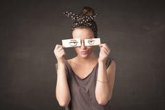 Persona joven que se sostiene de papel con el dibujo enojado del ojo Imágenes de archivo libres de regalías