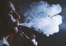 Persona joven que sostiene el cigarrillo electrónico o el cig de e y vaping el cl Foto de archivo libre de regalías