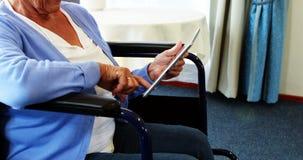 Persona jubilada en silla de rueda usando la tableta almacen de metraje de vídeo