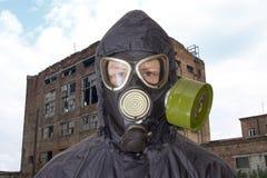 Persona in maschera antigas contro il contesto di costruzione abbandonata fotografia stock libera da diritti