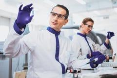 Persona masculina alegre que trabaja en laboratorio Imágenes de archivo libres de regalías