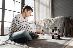 Persona masculina joven encantada que juega con el robot Imágenes de archivo libres de regalías