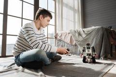 Persona masculina joven encantada que juega con el robot Imagen de archivo