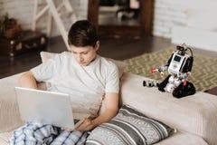 Persona masculina joven muy ocupada que juega a los juegos de ordenador Imagenes de archivo
