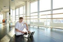 Persona masculina que aprende los nuevos movimientos con el ordenador portátil en el gimnasio fotos de archivo