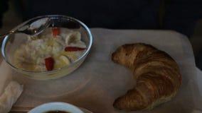 Persona masculina que come las gachas de avena con las frutas y el cruasán en café Desayuno, almuerzo almacen de metraje de vídeo