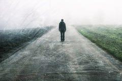 Persona masculina que se coloca en el camino de niebla foto de archivo