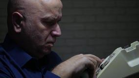 Persona mayor en oscuridad de la oficina con el dial disponible del teléfono un número de teléfono almacen de video