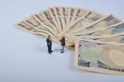 Persona minúscula que se coloca en un enorme del dinero Imagen de archivo libre de regalías