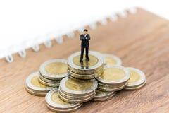 Persona miniatura: Figura del hombre de negocios que se coloca en la pila de monedas Uso de la imagen para el negocio, concepto f Imagen de archivo