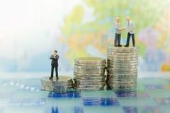 Persona miniatura: Figura del hombre de negocios que se coloca en la pila de monedas Uso de la imagen para el negocio, concepto f Imagenes de archivo
