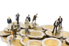 Persona miniatura: Hombre de negocios que se coloca en la pila de monedas Uso de la imagen para el negocio, concepto financiero Imagenes de archivo