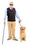 Persona oculta que sostiene un bastón y un perro