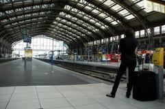 Persona posteriore che aspetta un treno su un binario della stazione ferroviaria immagini stock libere da diritti