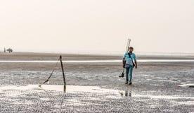 Persona que camina con la cámara y el trípode en la playa Imagenes de archivo