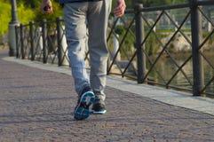Persona que camina con las zapatillas de deporte y los vaqueros Imagen de archivo
