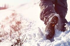 Persona que camina en la cima de la montaña cubierta con la opinión de ángulo bajo de la nieve fotos de archivo