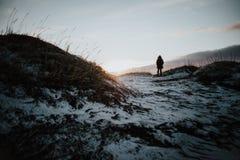 Persona que camina en Stokksnes, Islandia en la puesta del sol Fotos de archivo libres de regalías