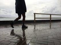 Persona que camina, lluvia que cae en el pavimento Imagenes de archivo