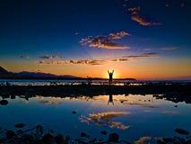 Persona que celebra en la puesta del sol imagen de archivo