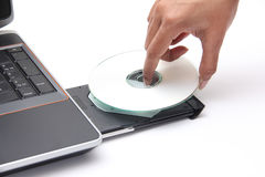 Persona que coloca un disco compacto en el lector de CD-ROM Imagen de archivo libre de regalías