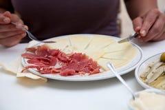 Persona que come el queso y las carnes frías imagenes de archivo