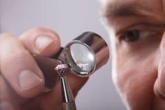 Persona que comprueba a Diamond Through Magnifying Loupe imágenes de archivo libres de regalías