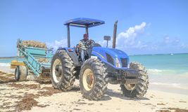 Persona que conduce un tractor y que limpia la playa fotografía de archivo libre de regalías