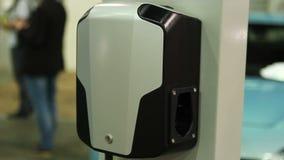 Persona que conecta y que desconecta el enchufe del vehículo eléctrico en la estación de carga almacen de metraje de vídeo