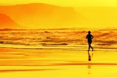 Persona que corre en la playa en la puesta del sol Imagen de archivo